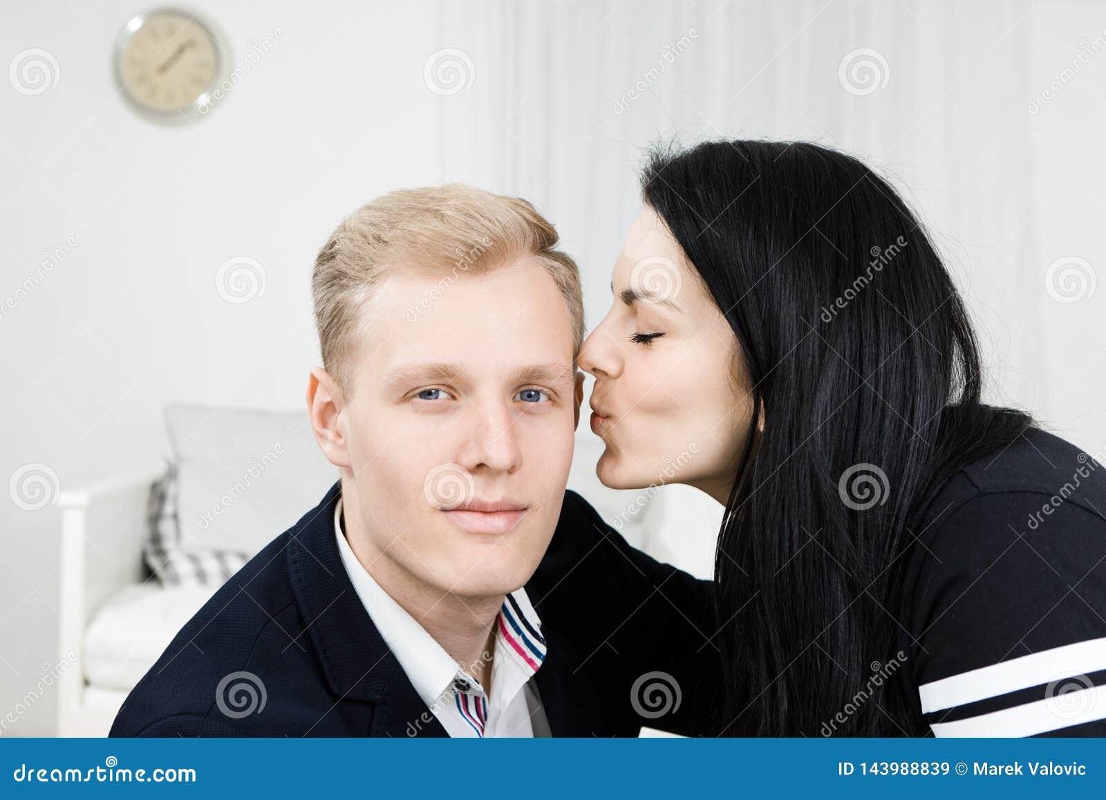 Ung attraktiv affärskvinna som kysser mannen i formell klänning