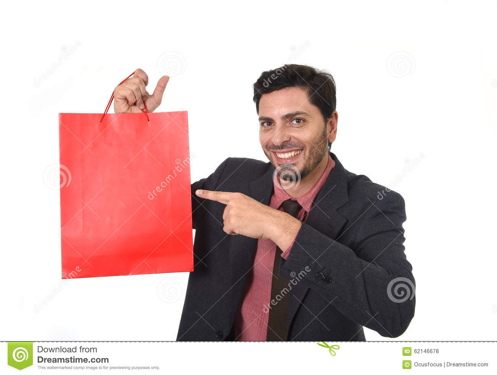 Ung attraktiv affärsman som rymmer och pekar den röda shoppingpåsen i försäljningsbegreppet som utför som representant