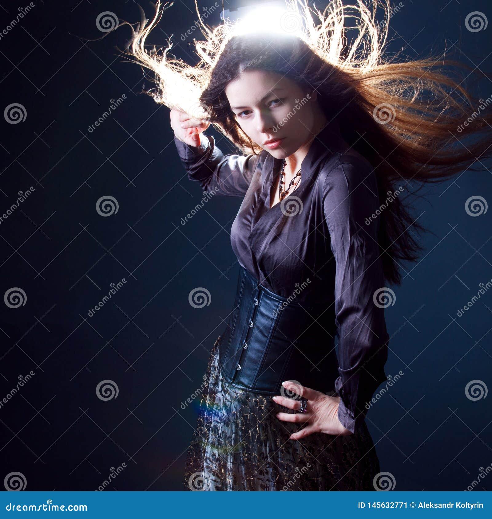 Ung attraktiv brunettkvinna i mörker Härlig ung häxabild för allhelgonaafton