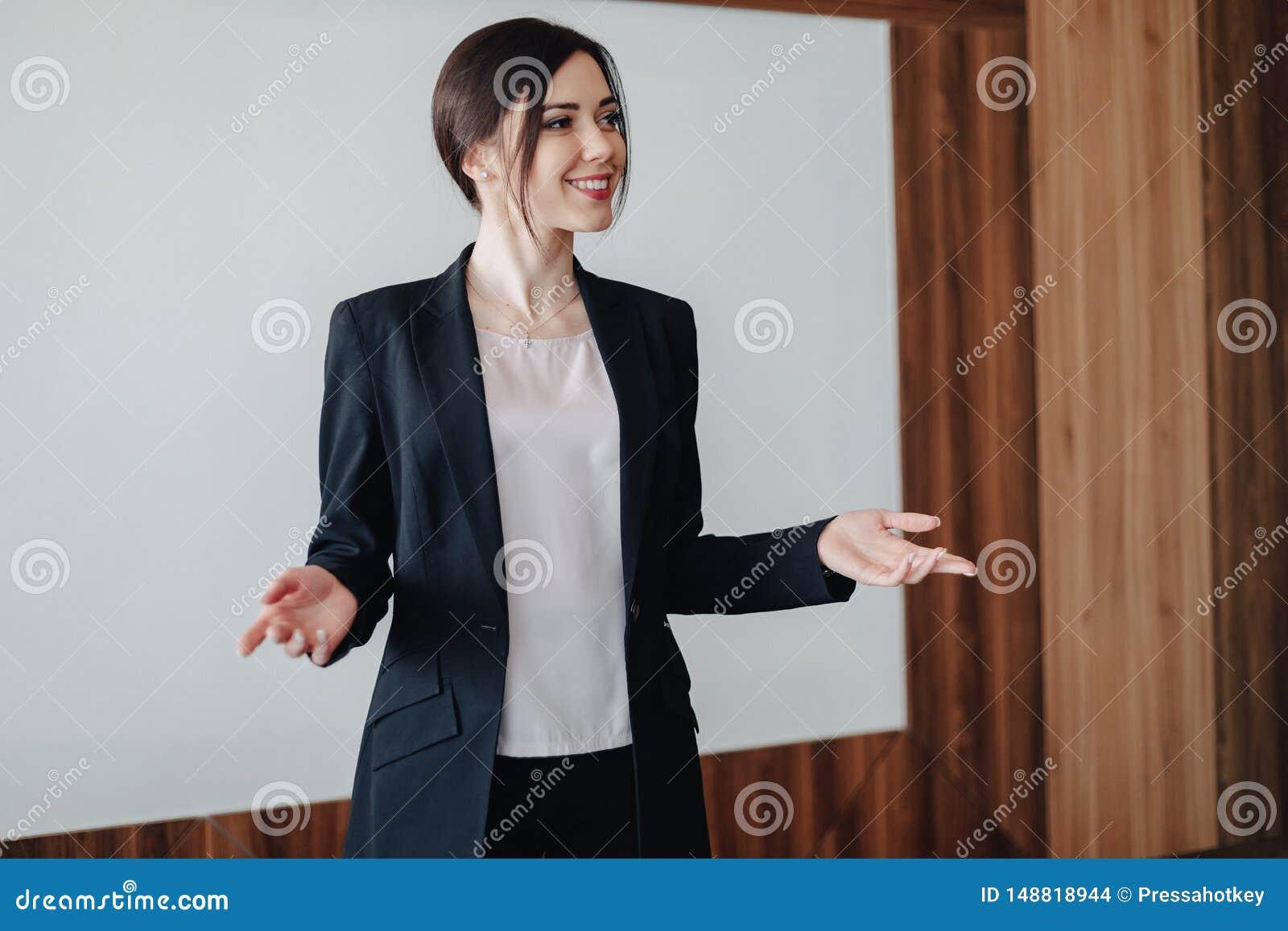 Ung attraktiv emotionell flicka i aff?r-stil kl?der p? en vanlig vit bakgrund i ett kontor eller ?h?rare