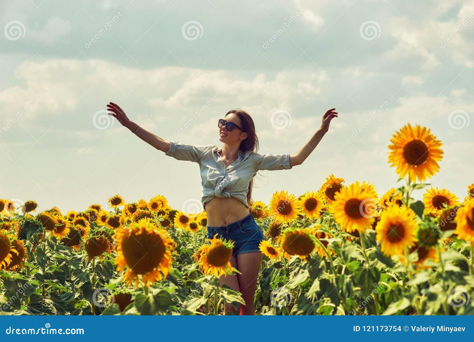 Ung attraktiv flicka i fältet med solrosor