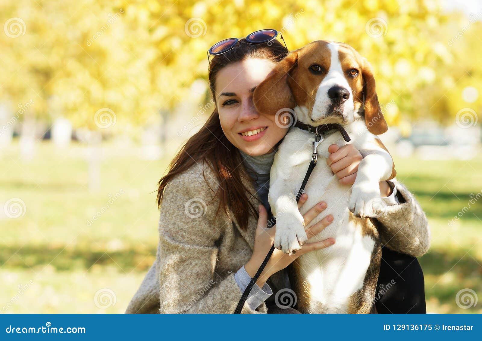 Ung attraktiv flicka som kramar hennes gulliga beaglehund
