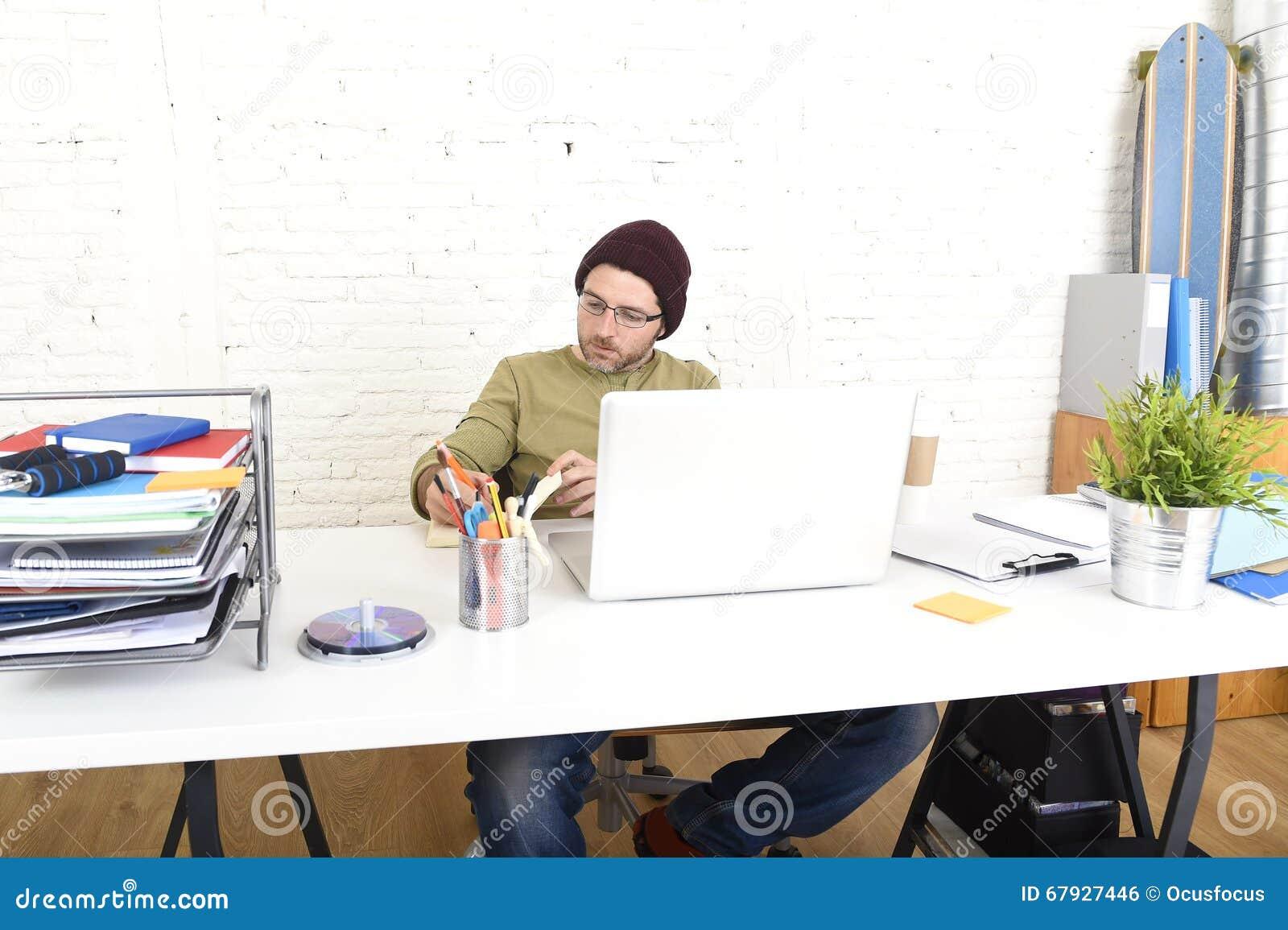 Ung attraktiv hipsteraffärsman som arbetar från hans inrikesdepartementet som självständig affärsmodell för freelancer