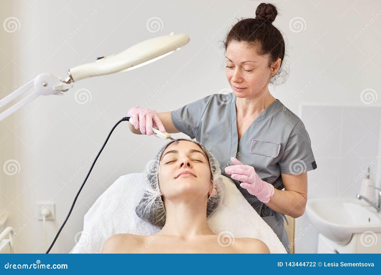Ung attraktiv kvinna som får ultraljuds- ansikts- hud som rentvår behandling av den yrkesmässiga cosmetologisten, i skönhetsalong