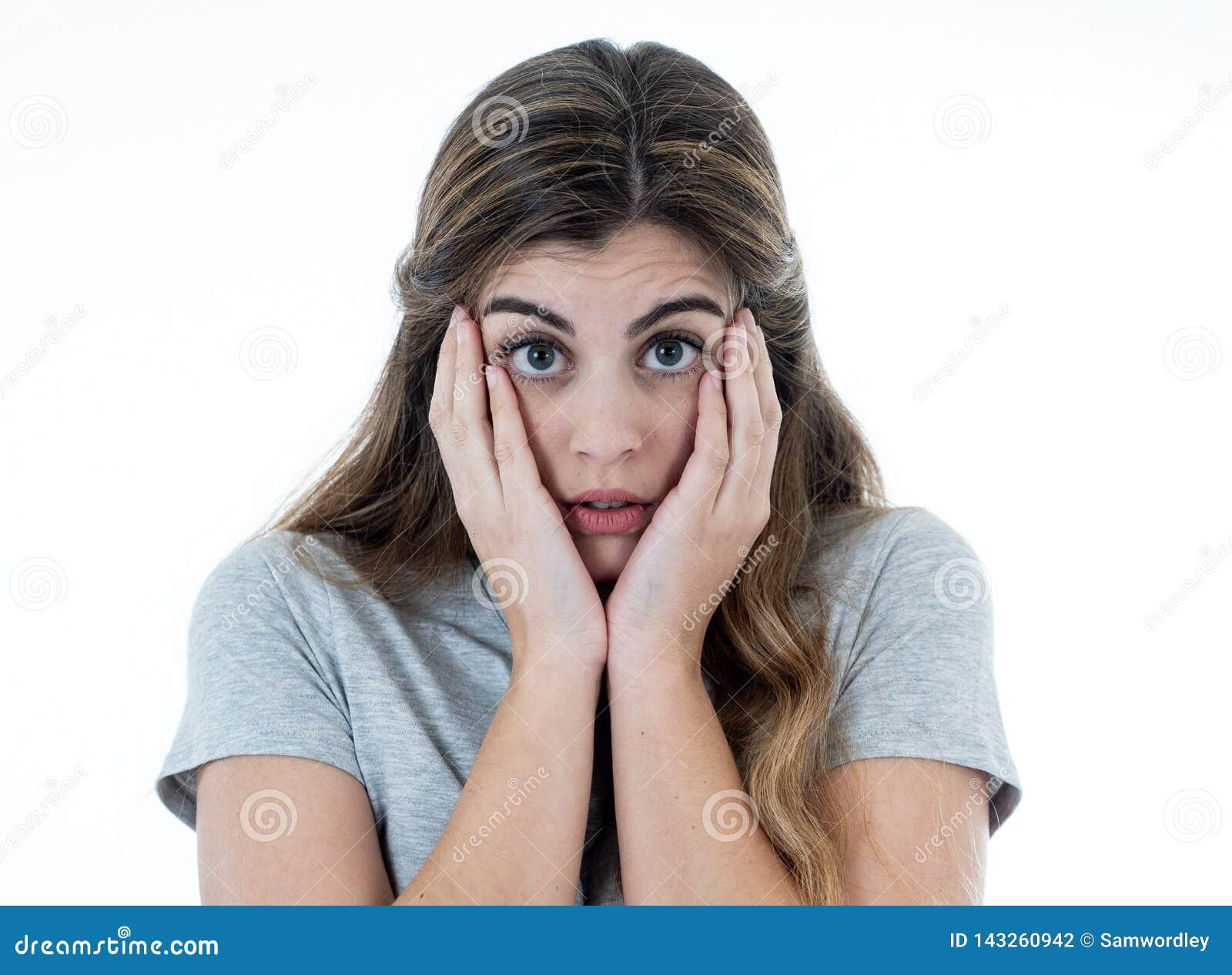 Ung attraktiv kvinna som ser skrämd, skrämd och chockad Mänskliga uttryck och sinnesrörelser