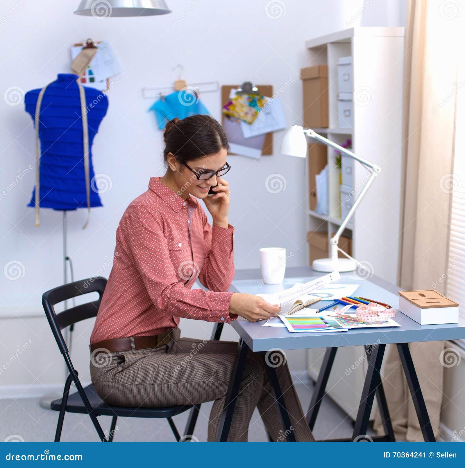 Ung attraktiv kvinnligmodeformgivare som fungerar på kontorsskrivbordet som tecknar, medan tala på mobil
