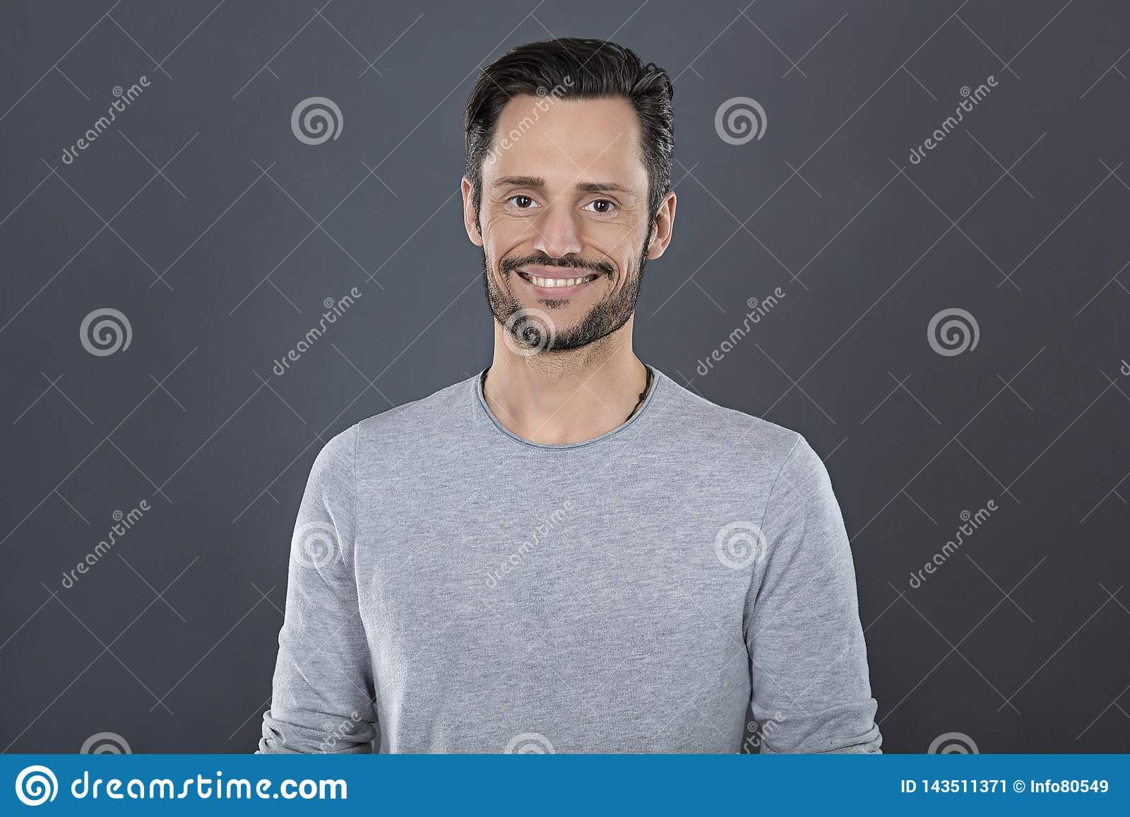 Ung attraktiv man med grått t-skjorta le som är lyckligt framme av en grå bakgrund