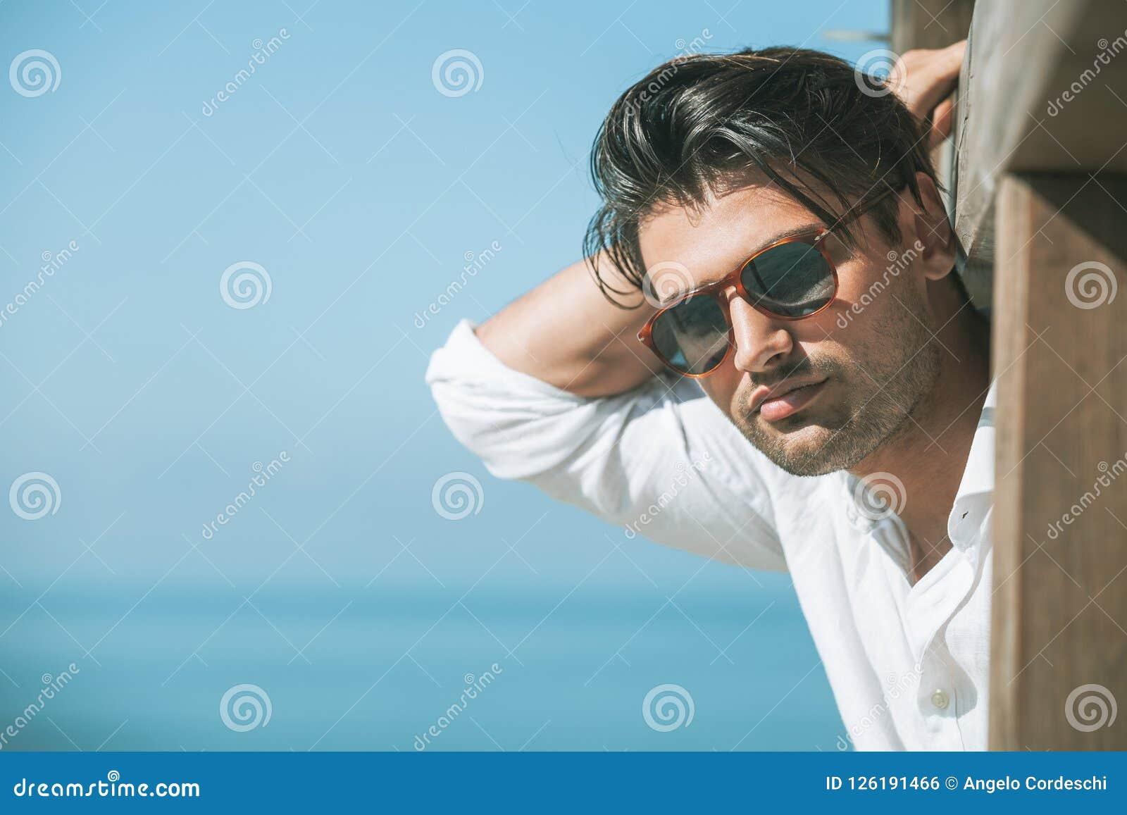 Ung attraktiv man med solglasögon som ut ser över havet under sommaren