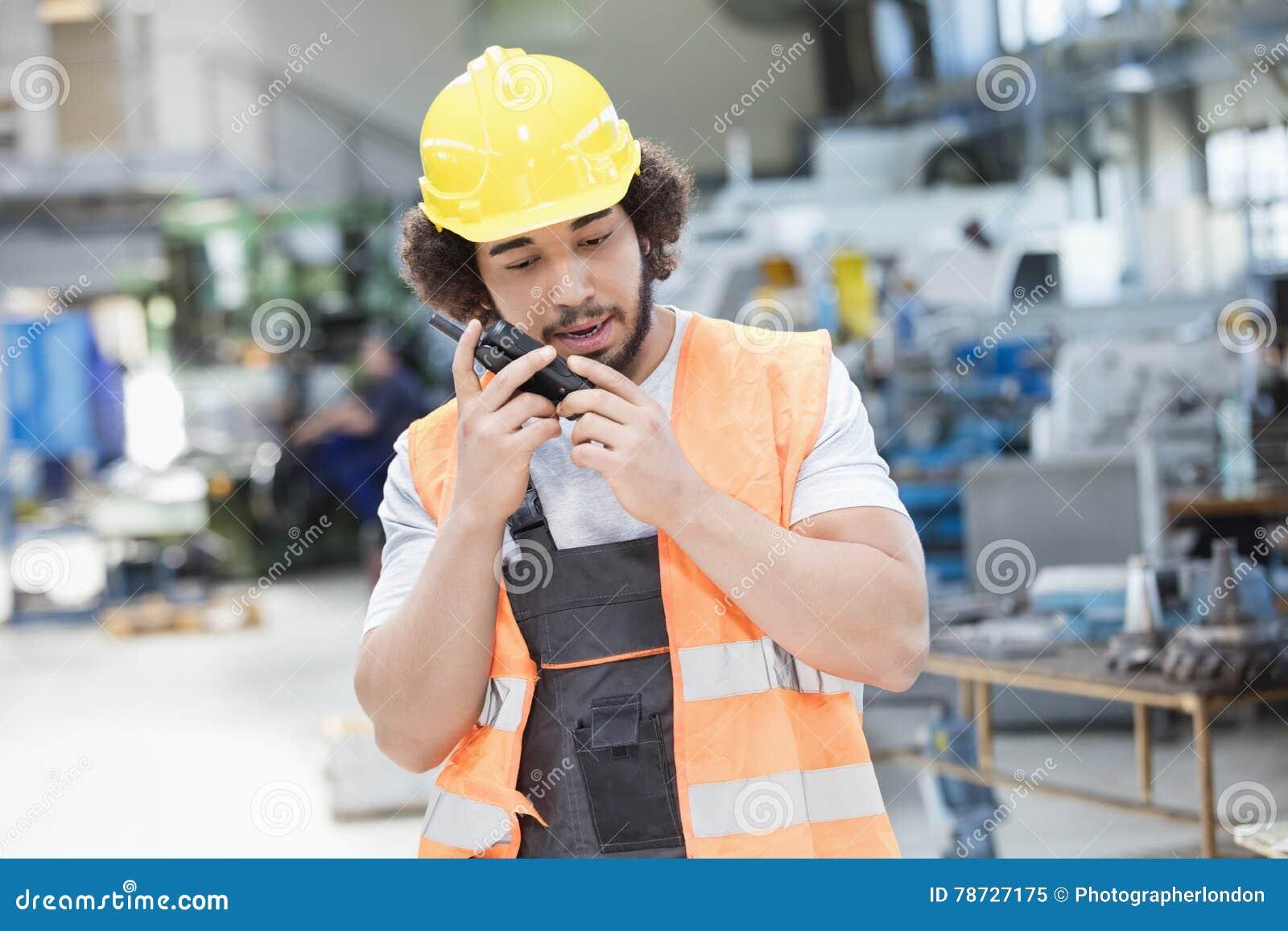 Ung bärande skyddskläder för manuell arbetare, medan genom att använda walkie-talkie i metallbransch