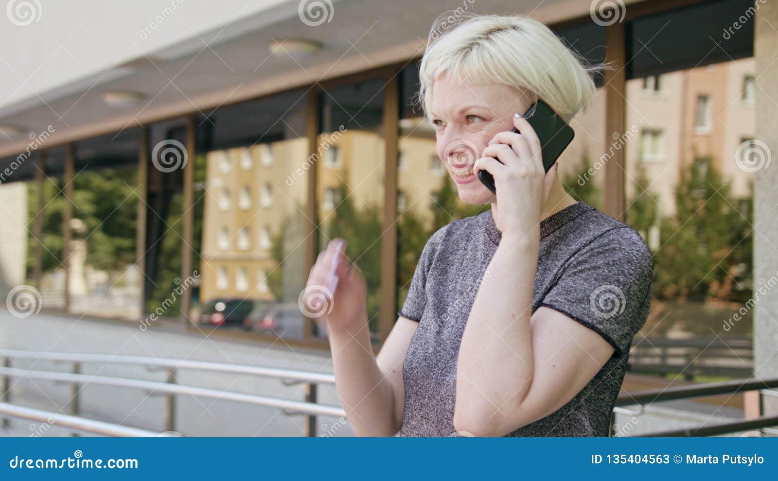 Ung blond dam Speaking på telefonen i stad