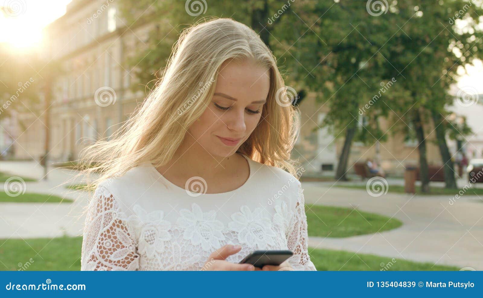 Ung blond dam Walking och använda en telefon i stad