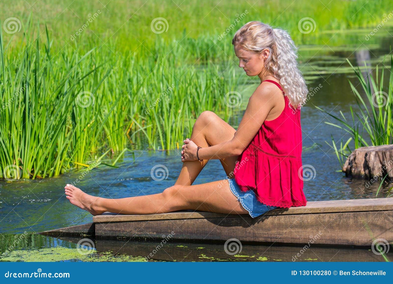 Ung blond kvinna som dagdrömmer på vatten i natur