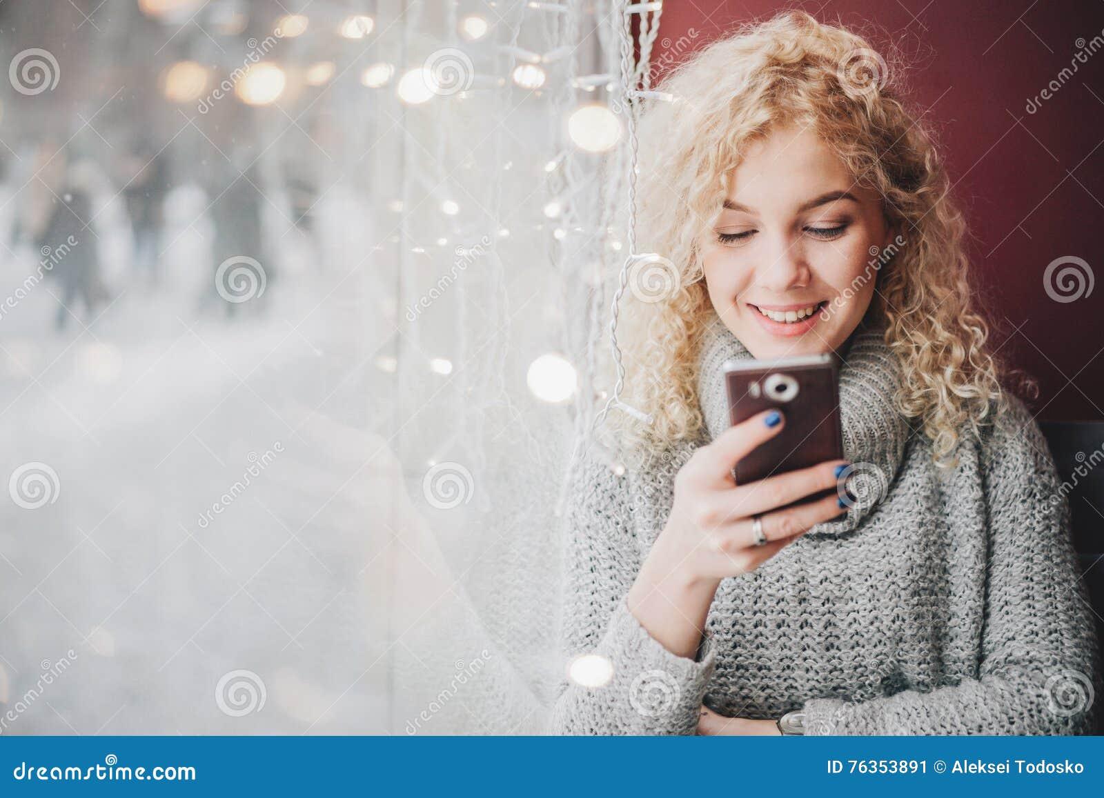 Ung blond lockig härlig kvinnlig som ler genom att använda en smartphone