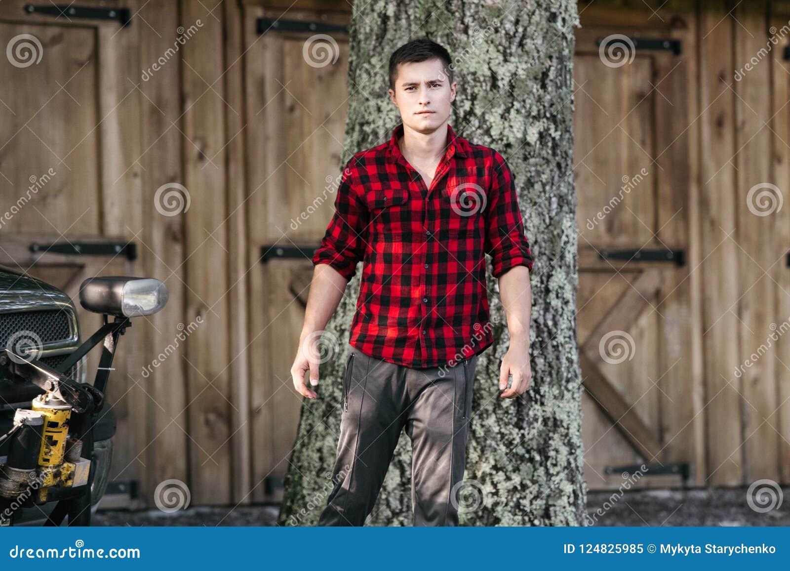 Ung bondeman som går på hans lantgård nära träladugården som bär den röda t-skjortan