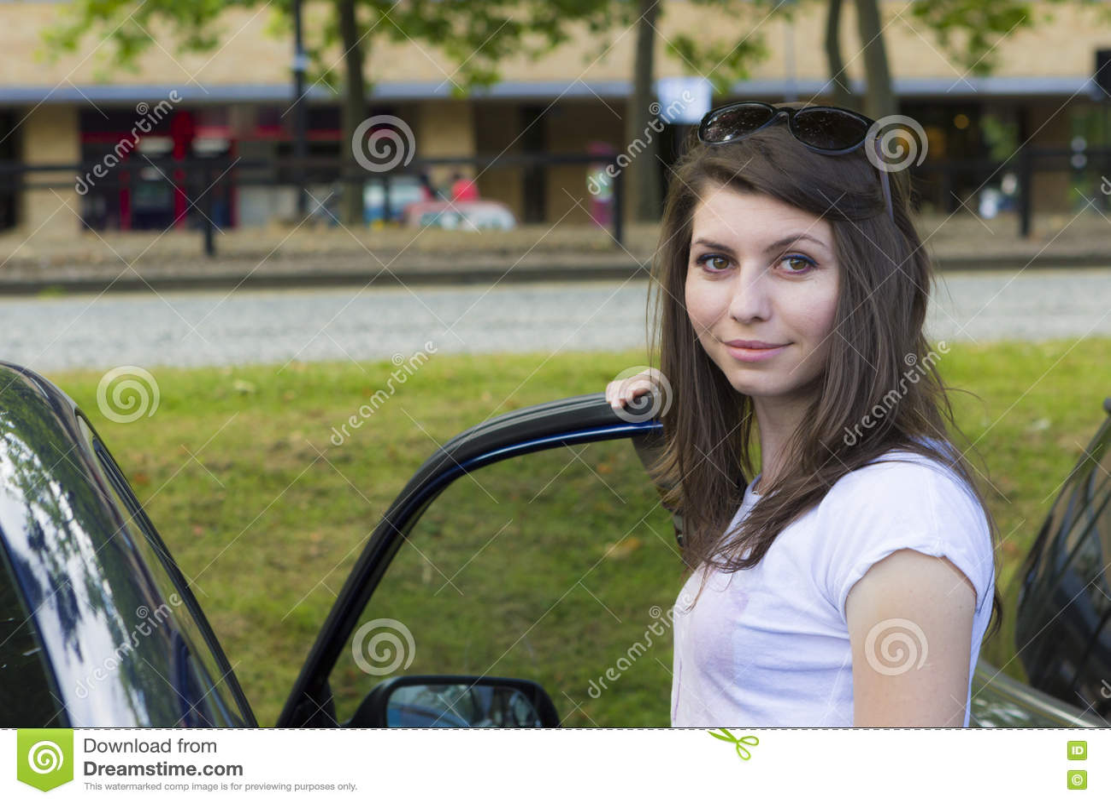 Ung brunett som poserar nära bilen