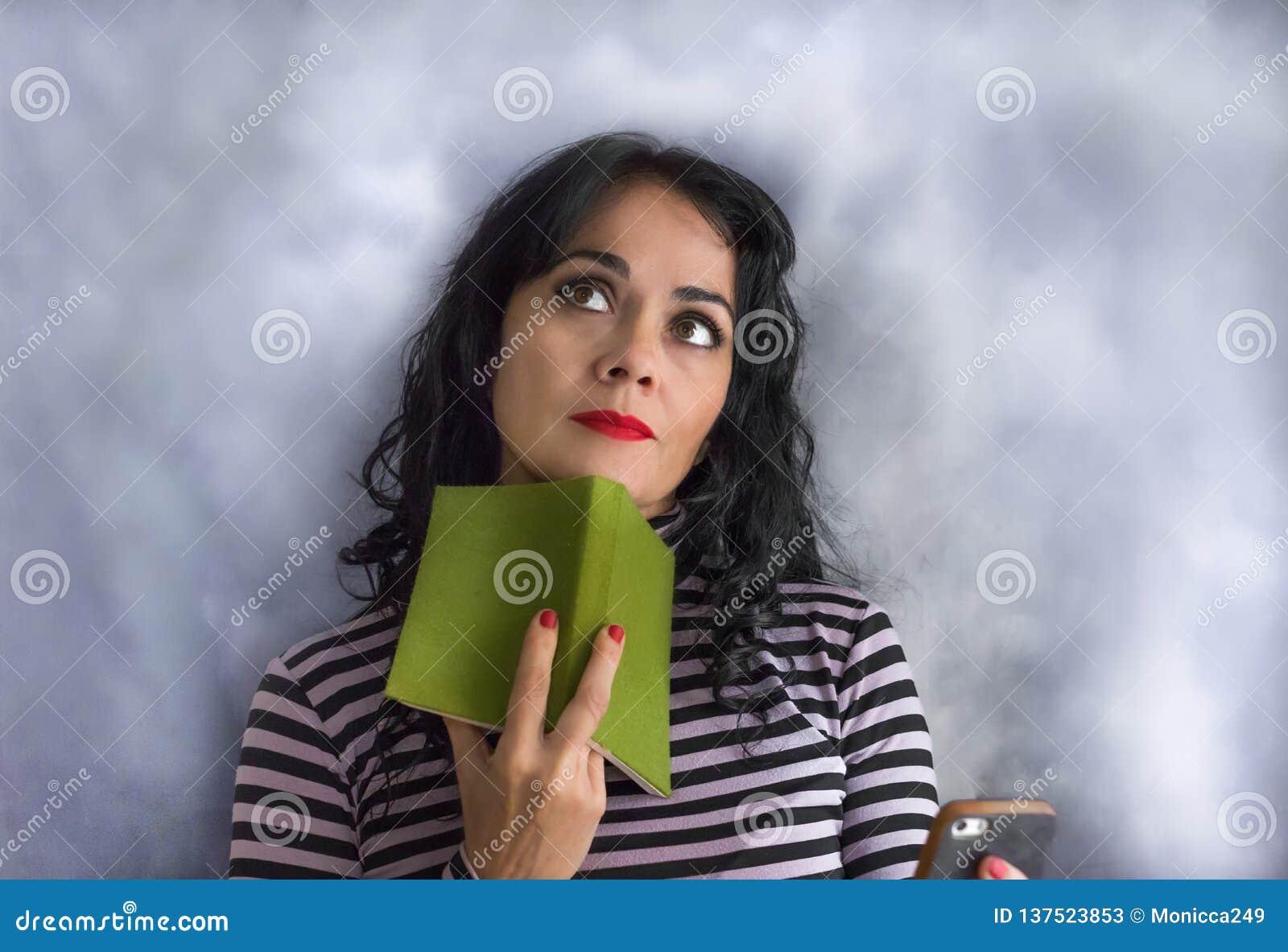 Ung brunettkvinna med den randiga tröjan med en bok på hennes haka som tänker om en fråga