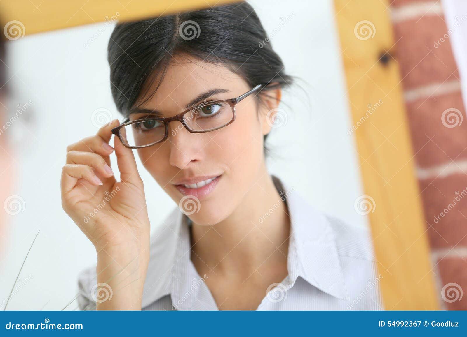 Ung brunettkvinna som ser spegeln