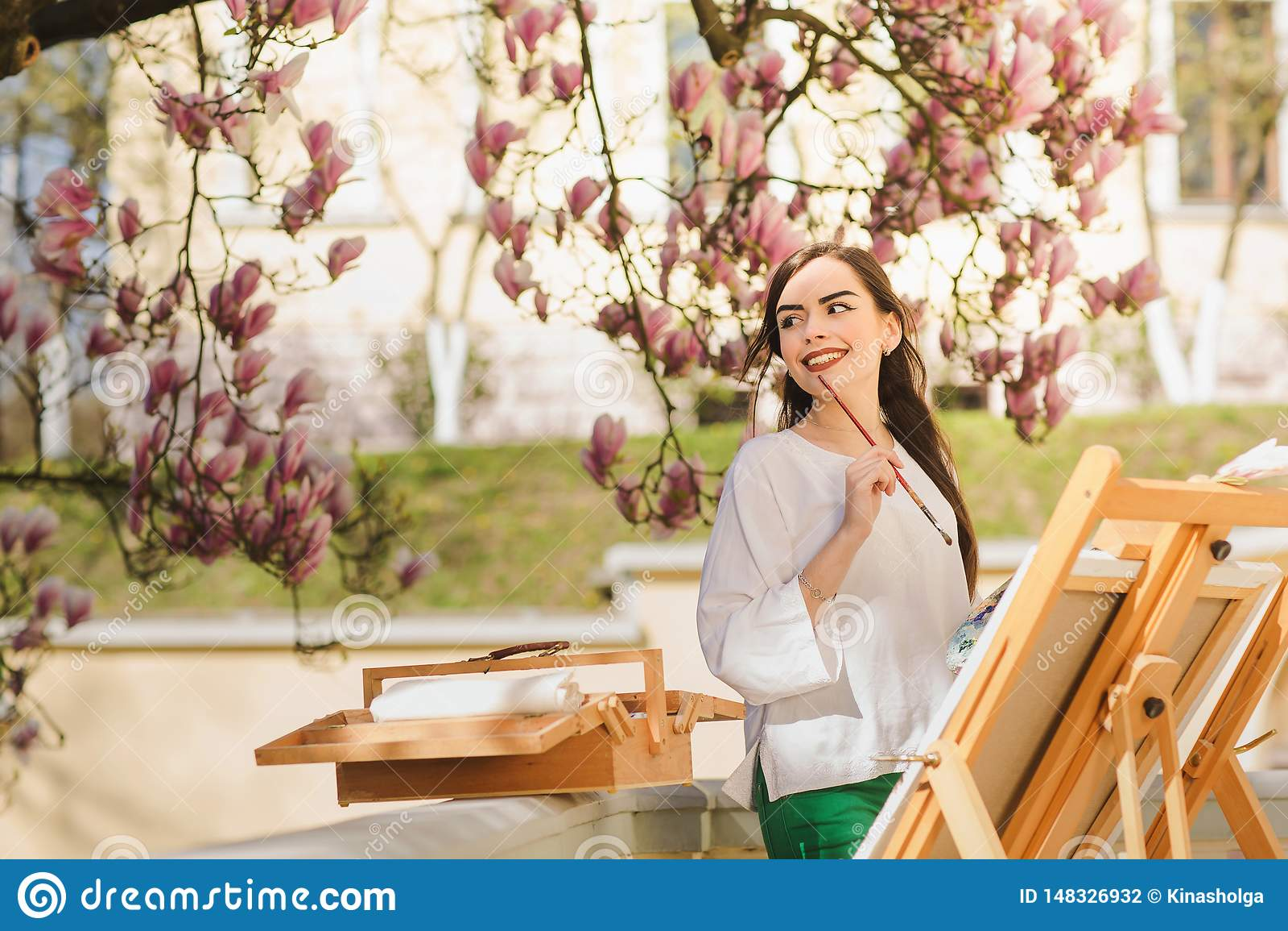 Ung brunettkvinnakonstn?r som rymmer i h?nder en borste och en palett N?ra henne magnoliatr?det och den olika konstutrustningen