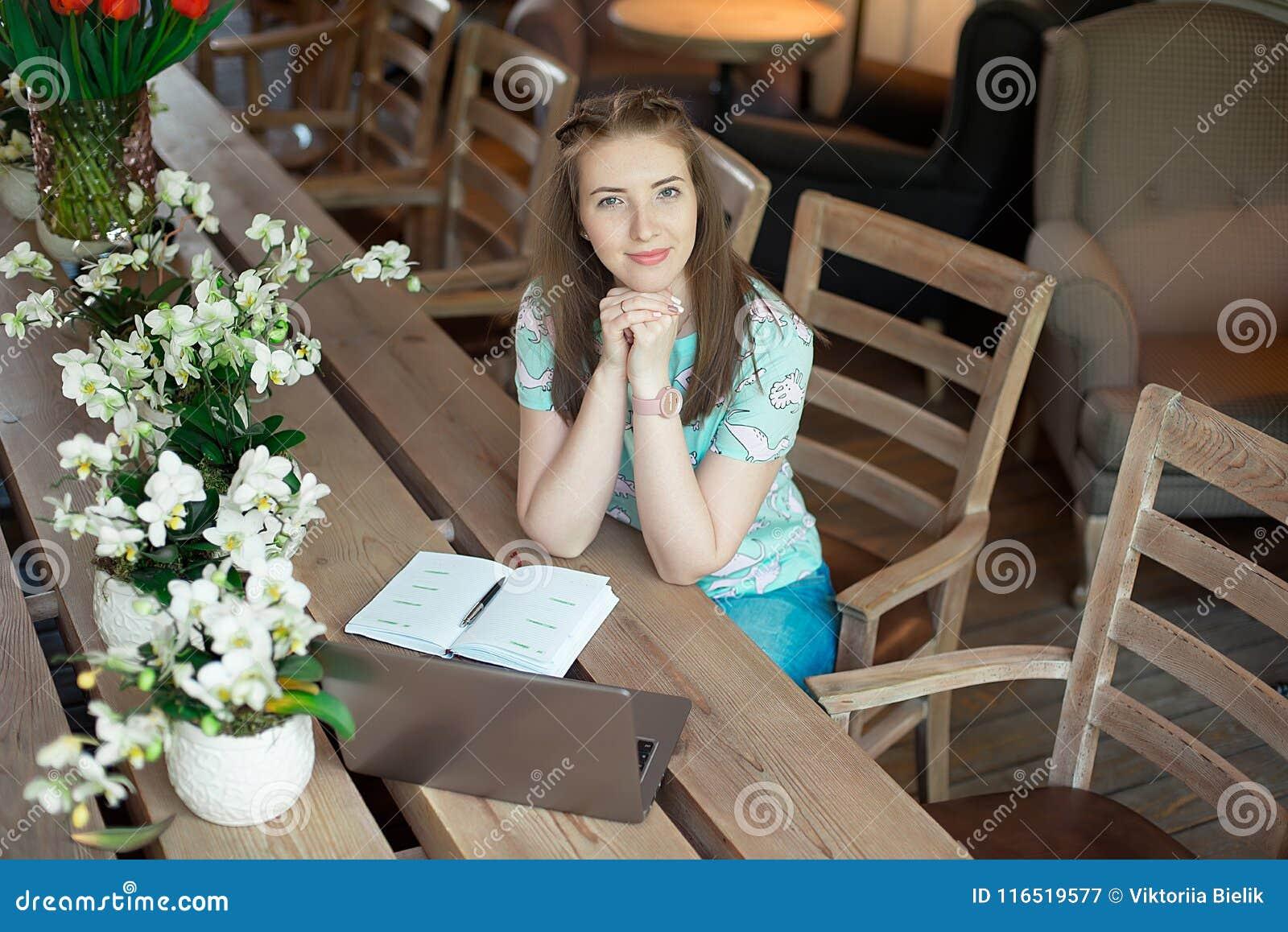 Ung caucasian affärskvinna i kafésammanträde på tabellen med fundersam stirrande