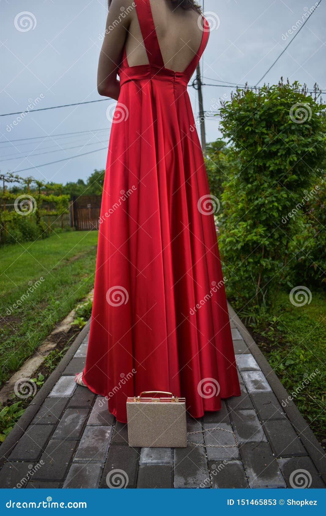 Ung caucasian flicka som bär den eleganta röda klänningen med den röda rosen i hennes hår