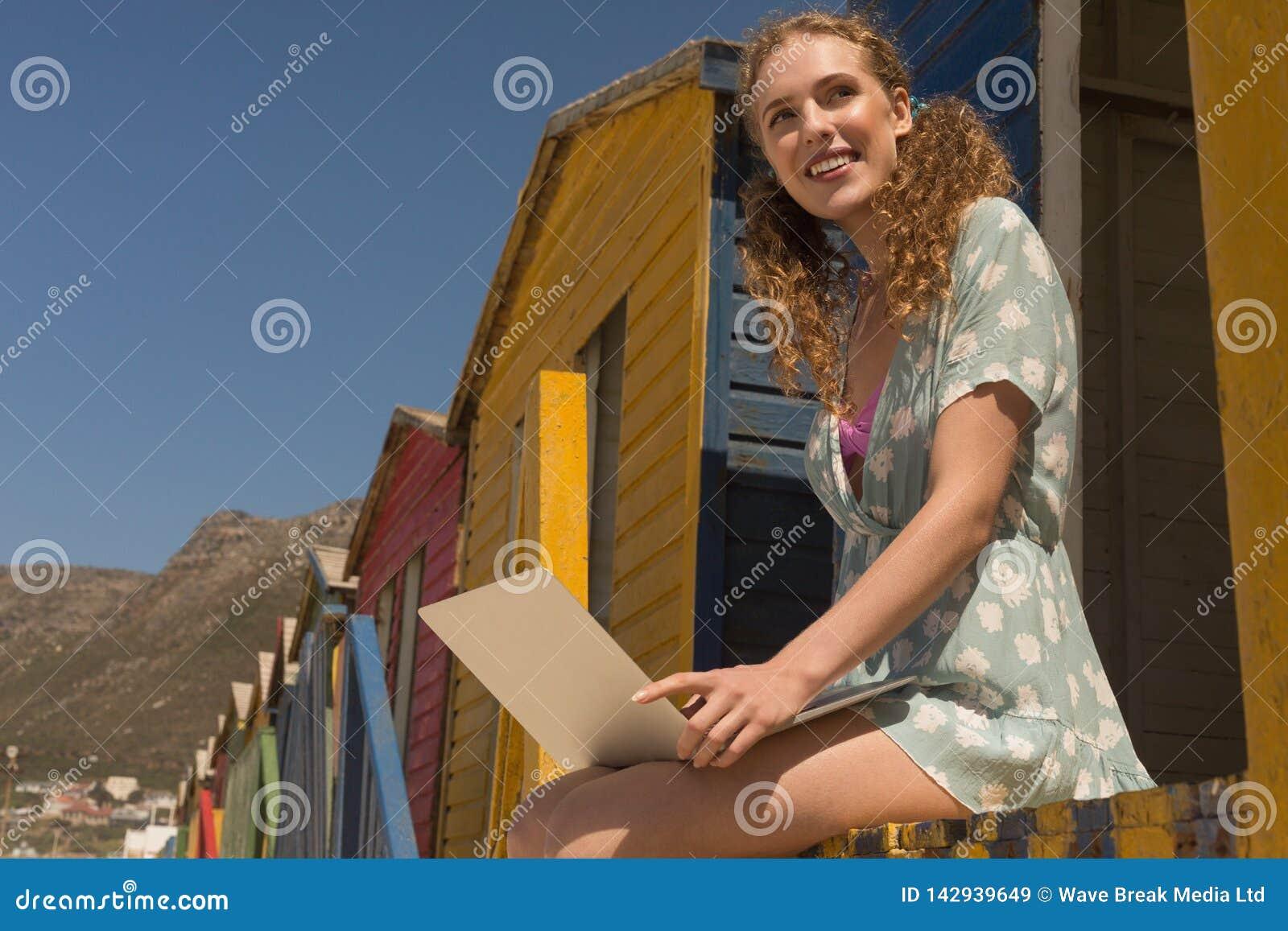 Ung Caucasian kvinna som använder bärbara datorn som bort ser på strandkojan