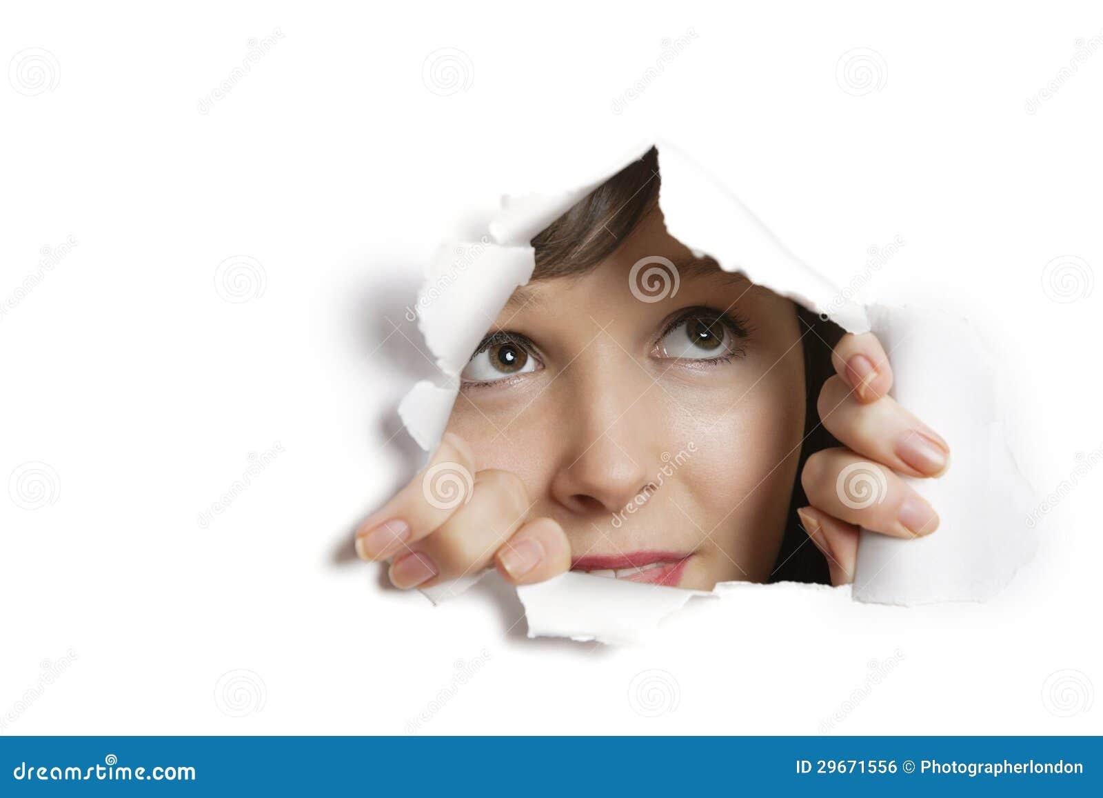 Ung Caucasian kvinna som kikar från det rev sönder pappers- hålet