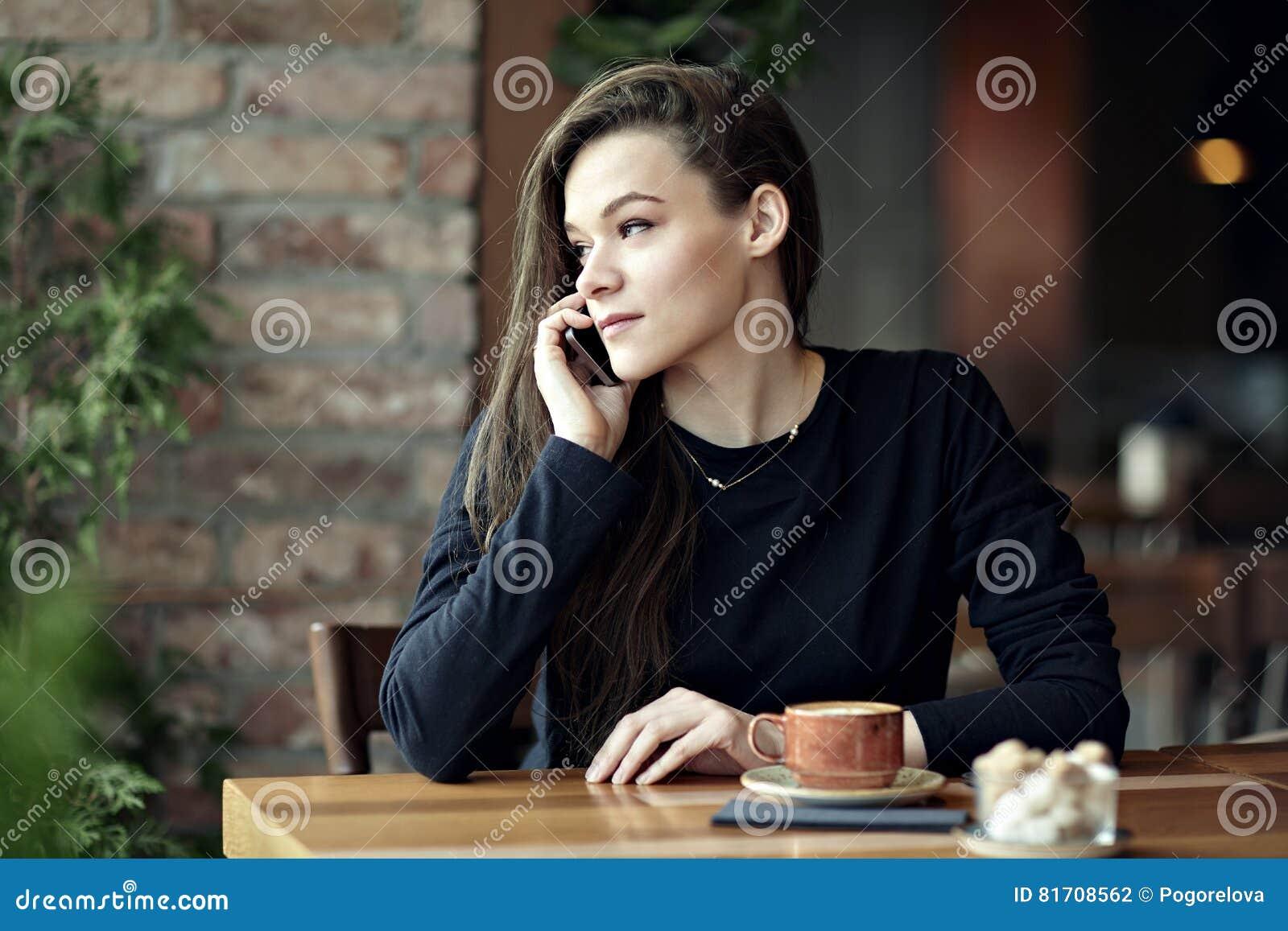 Ung caucasian kvinna som talar vid telefonen i en restaurang äganderätt för home tangent för affärsidé som guld- ner skyen till