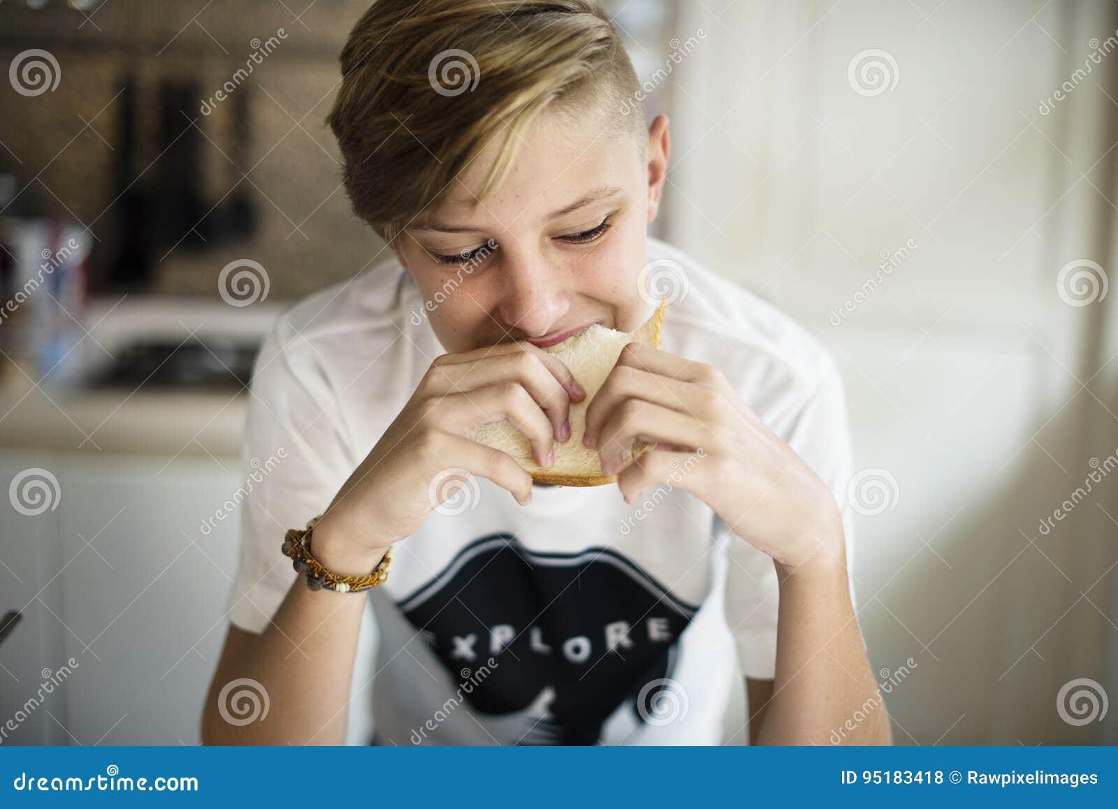 Ung caucasian man som äter smörgåsen i kök