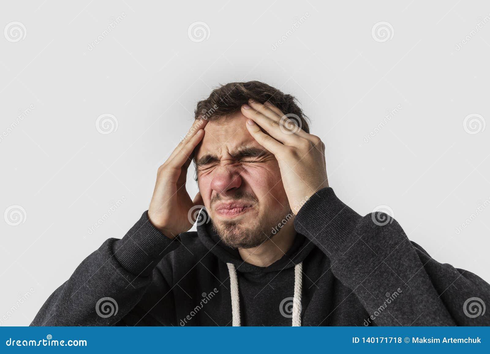 Ung caucasian man som lider från ruskig migrän bakgrund isolerad white Huvudvärkbegrepp
