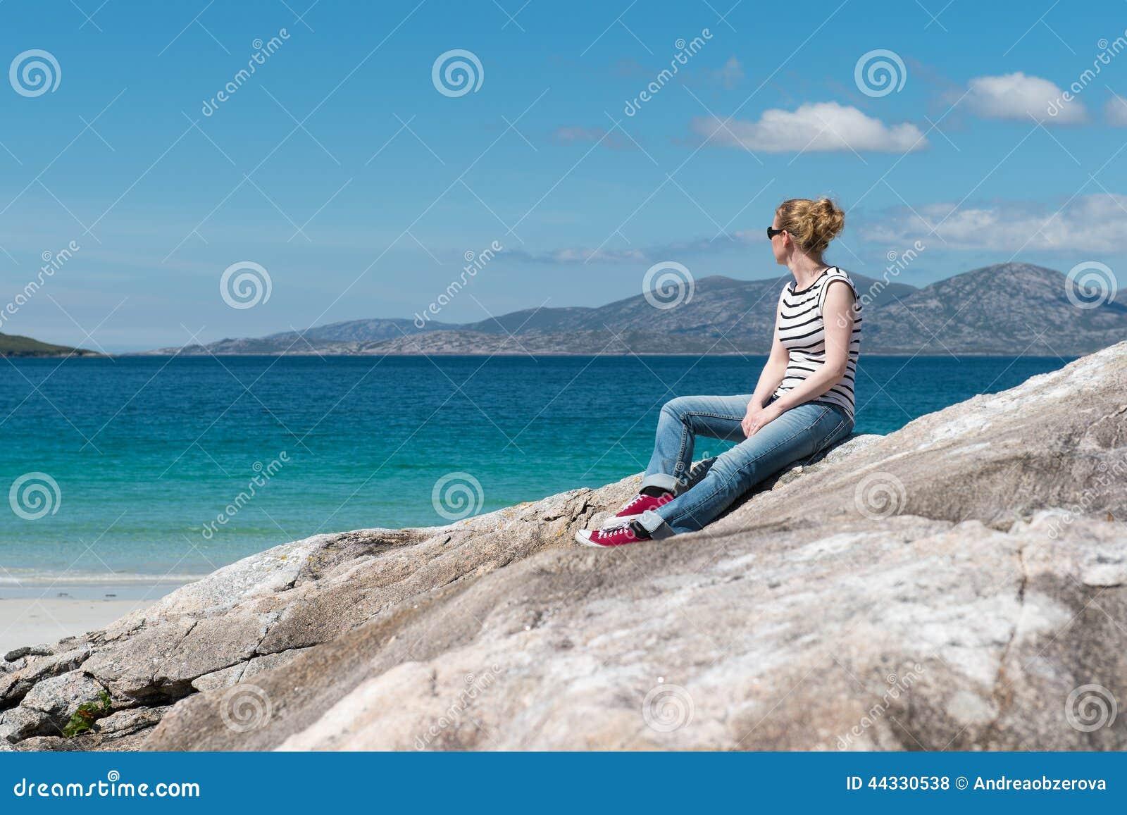 Ung Caucassian kvinna som tycker om ferie på en vit sandig strand med turkosvatten