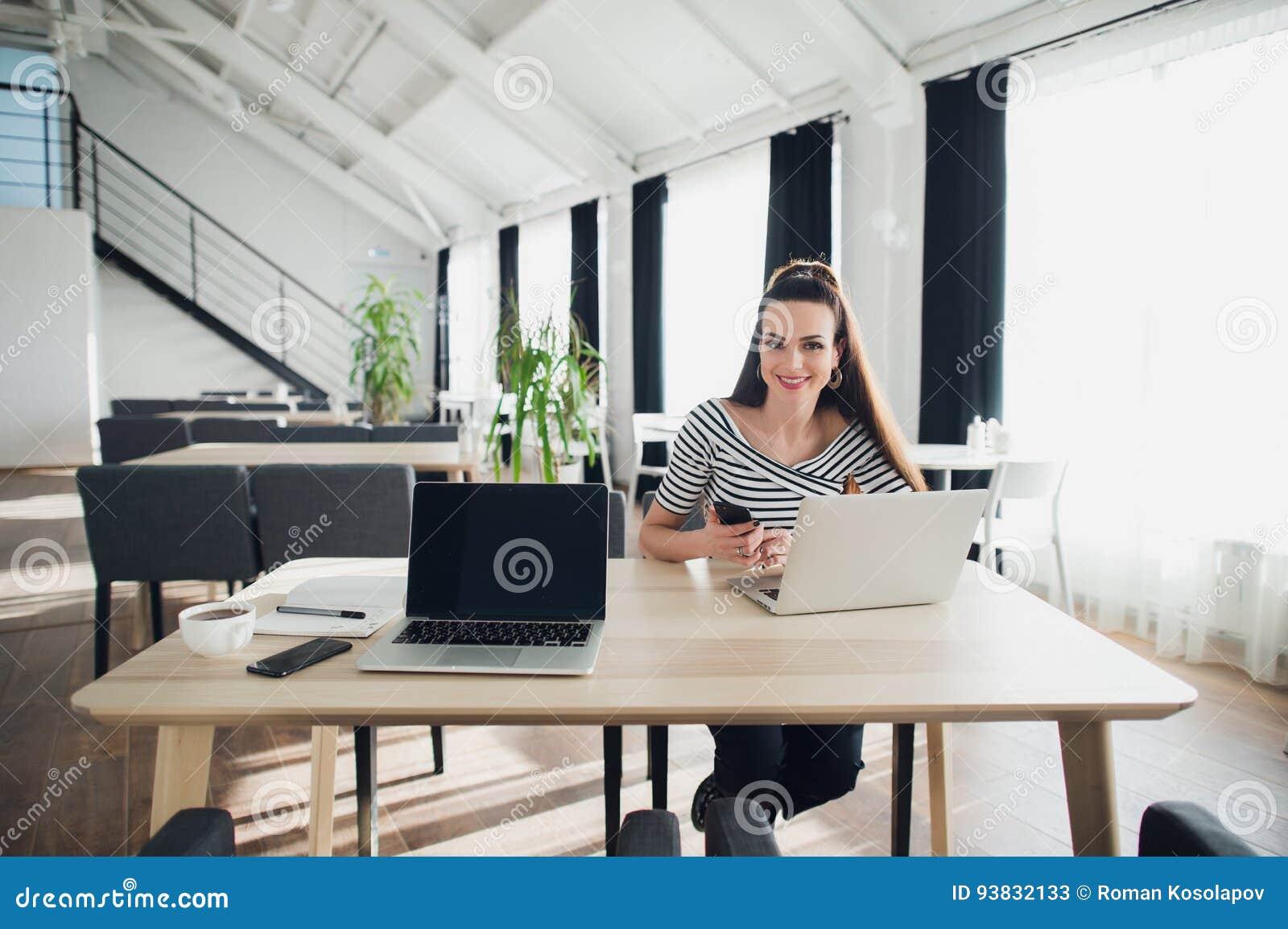 Ung charmig kvinna som kallar med celltelefonen, medan sitta bara i coffee shop under fri tid, attraktiv kvinnlig