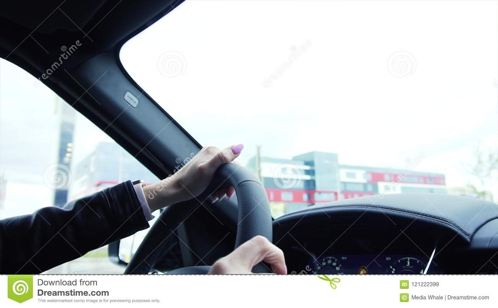 Ung chaufför för affärskvinna som kör en bil på en huvudväg materiel Stäng sig upp den unga härliga kvinnan som kör på en lyxig b
