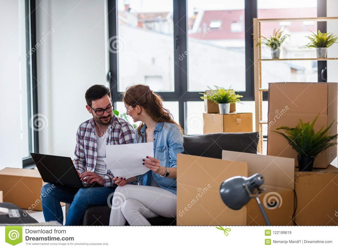 Ung Couple Moving In New Home Sitting And Relaxing After Unpacking