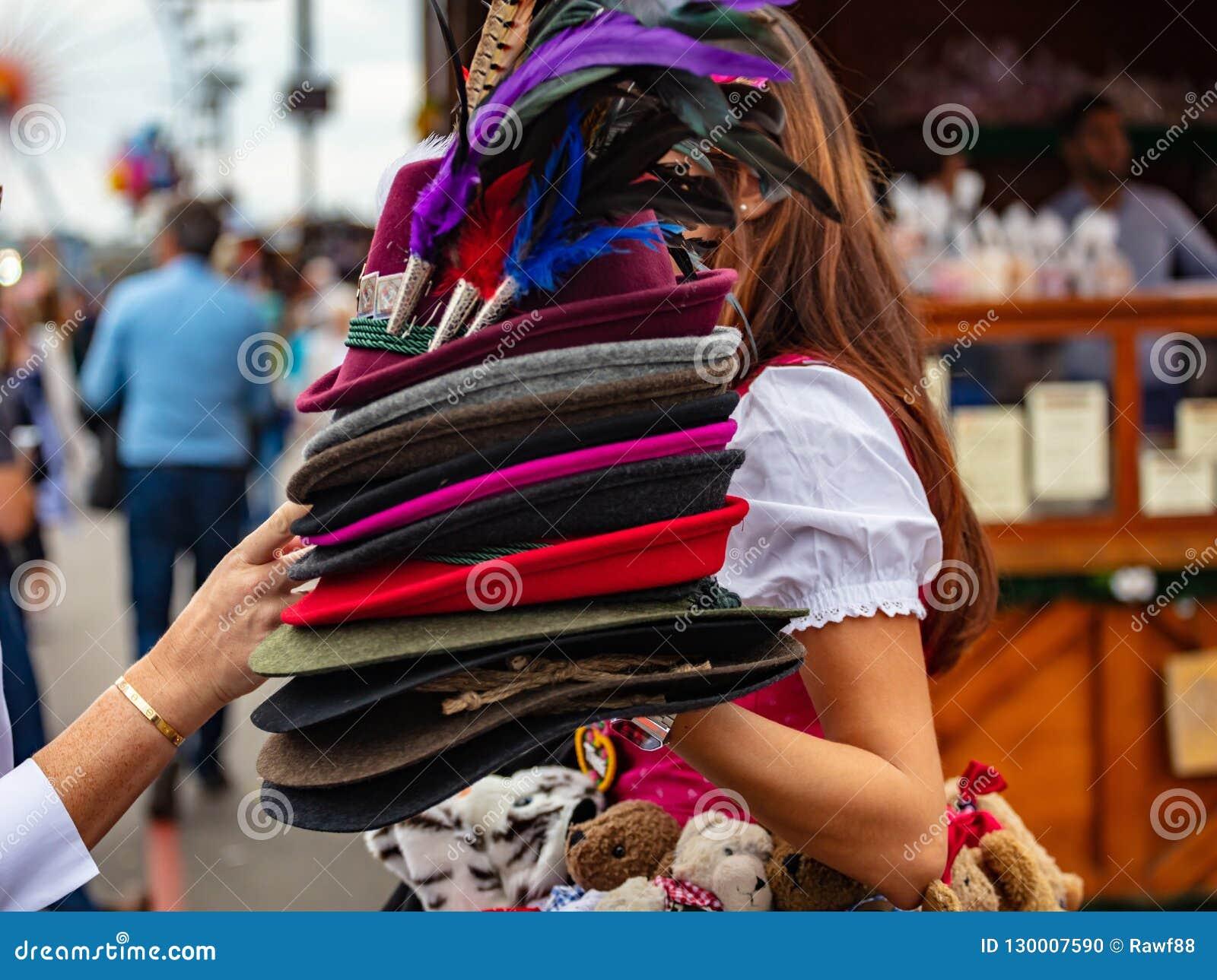 Ung dam i den tyrolean dräkten som rymmer en bunt av traditionella hattar, Oktoberfest, Munich, Tyskland
