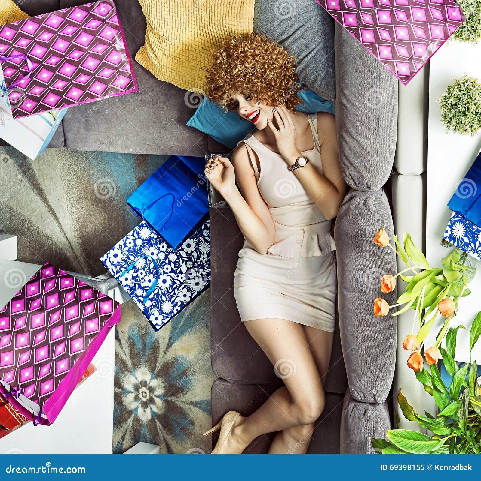 Ung dam med många shoppingpåsar som ligger på soffan