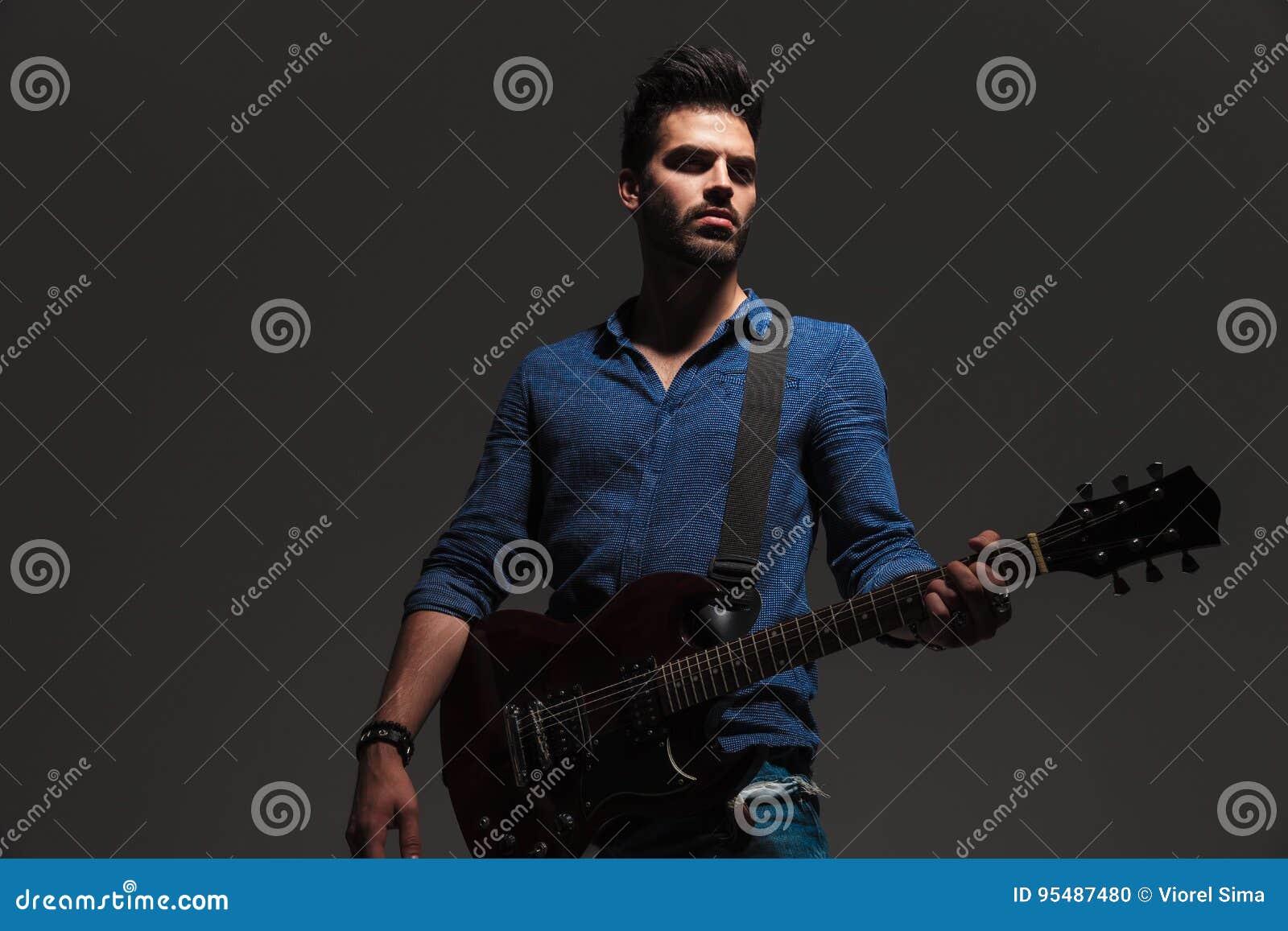 Ung dramatisk gitarrist som bort ser för att sid, medan spela