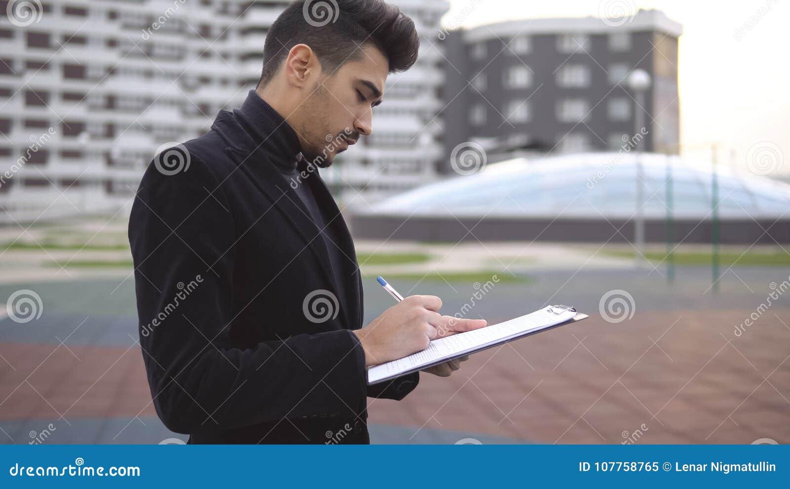 Ung företagsägare som tänker om ny produktidéer med penn- och pappersmappen