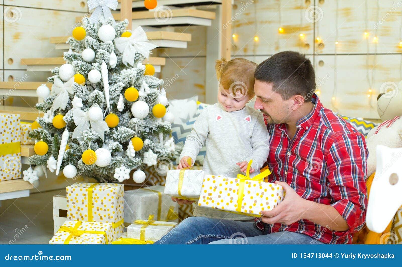 Ung fader- och litet barndotter som sitter nära julgranen och öppnande gåvaaskar