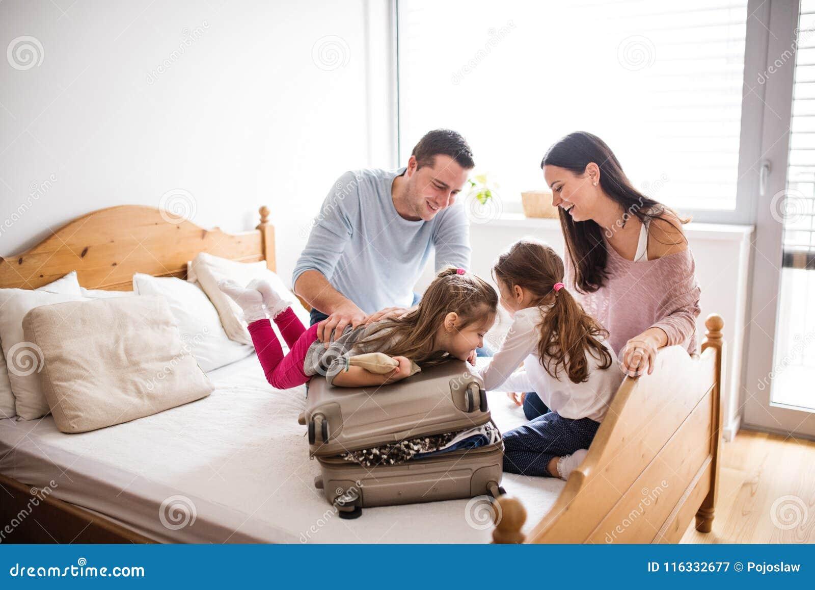 Ung familj med två barn som packar för ferie
