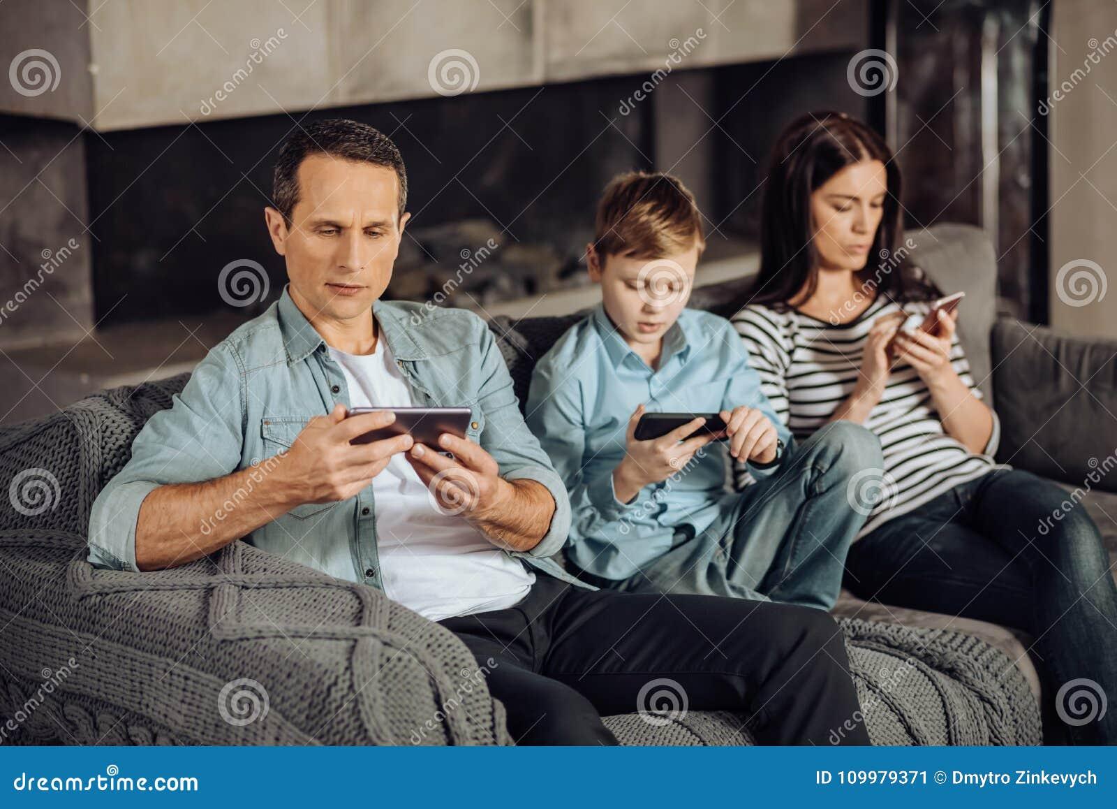 Ung familj som limmas till deras telefoner