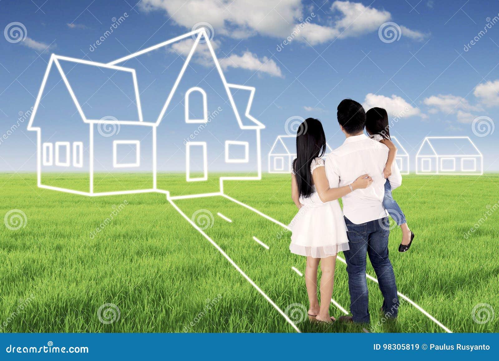 Ung familj som ser deras dröm- hus