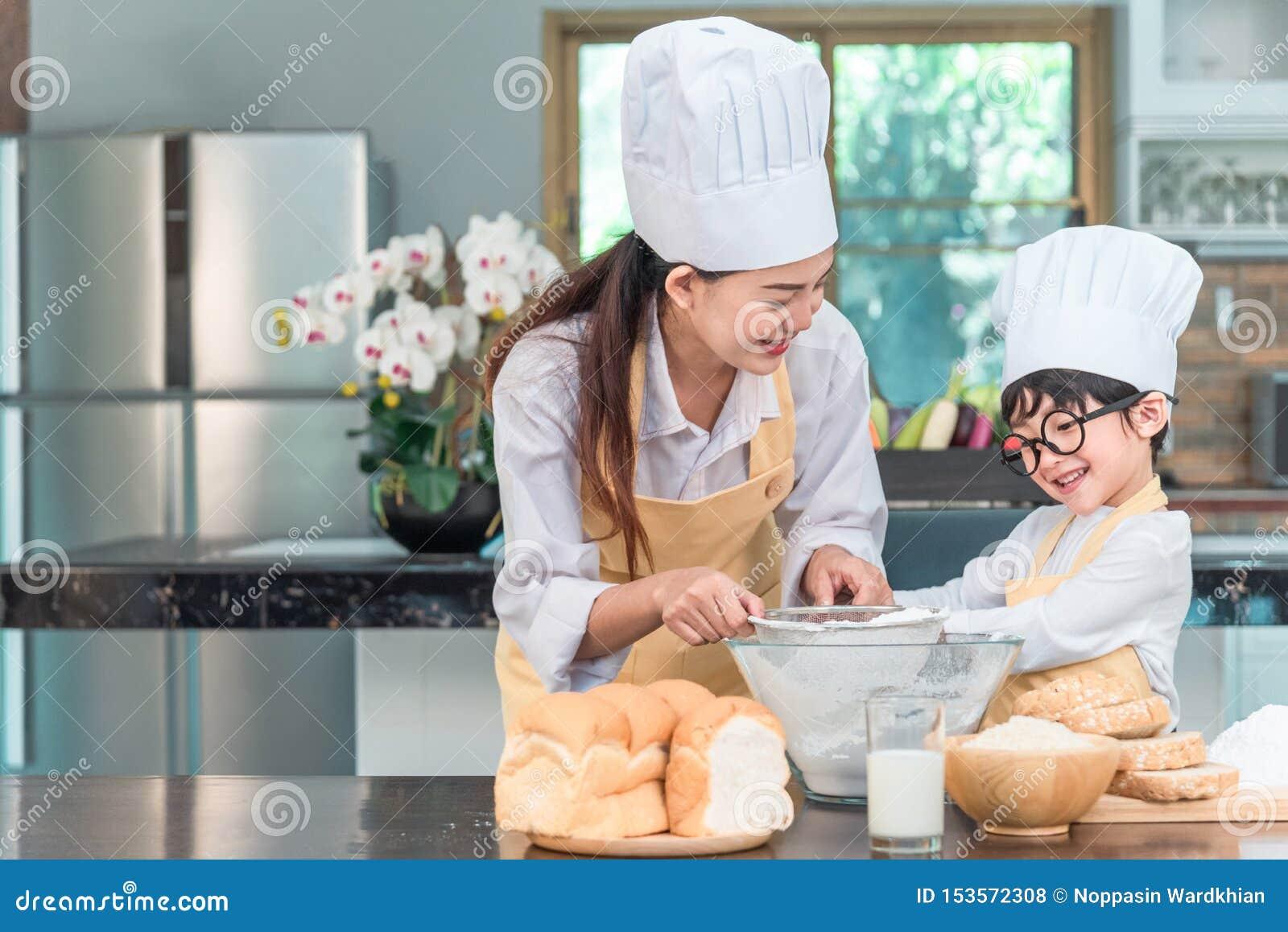 Ung familjmatlagningmat i k?k Lycklig ung flicka med hennes blandande smet f?r moder i bunken