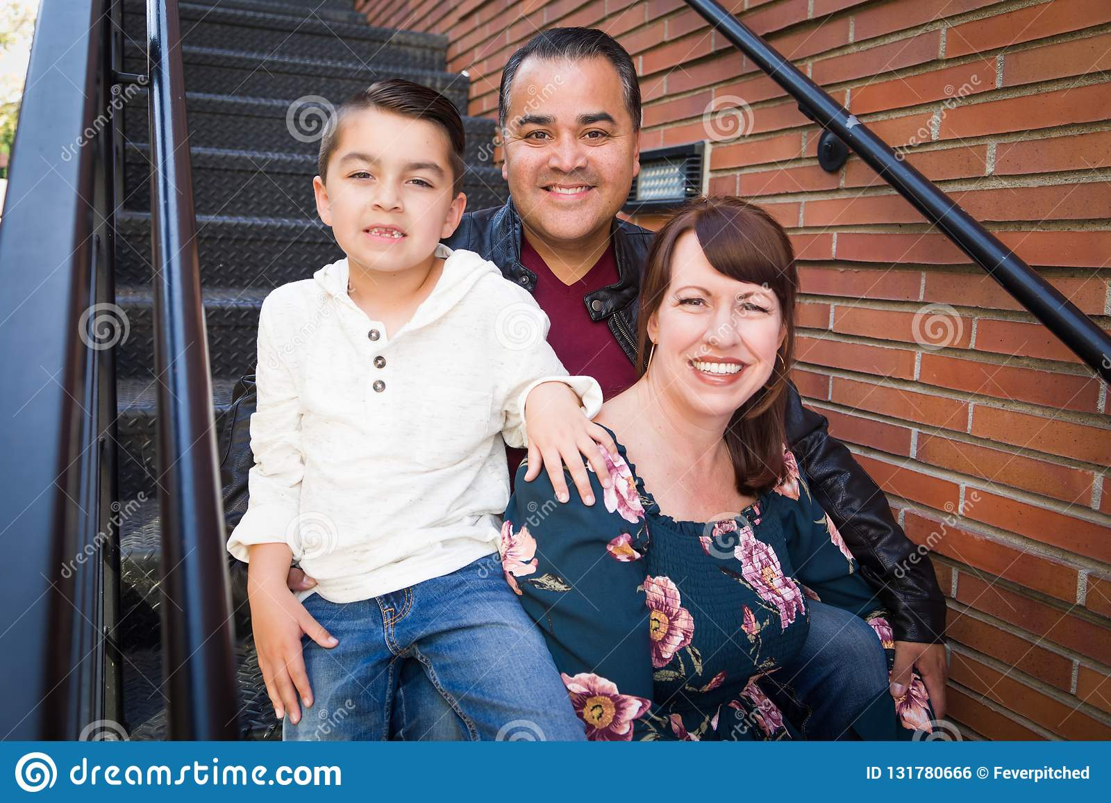 Ung familjstående för blandat lopp i en trappa