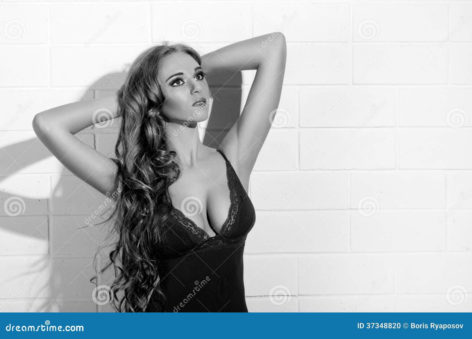 Ung flicka i brun underkläder på den vita väggen (den monokromma versionen)