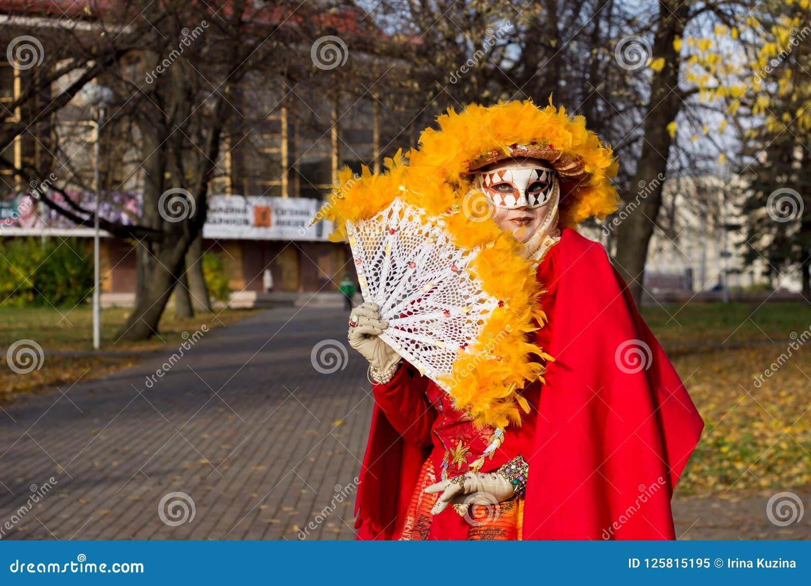 Ung flicka i en ` för dräkt`-höst i en karnevalmaskering