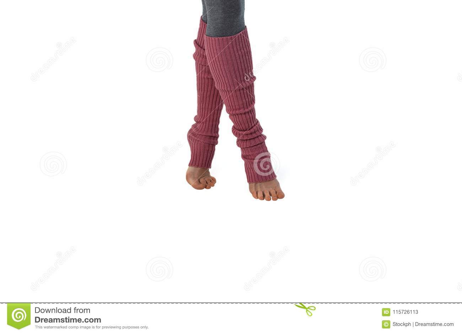 Ung flicka i rosa damasker som är förlovad i pilates som står på fingrar Vit bakgrund