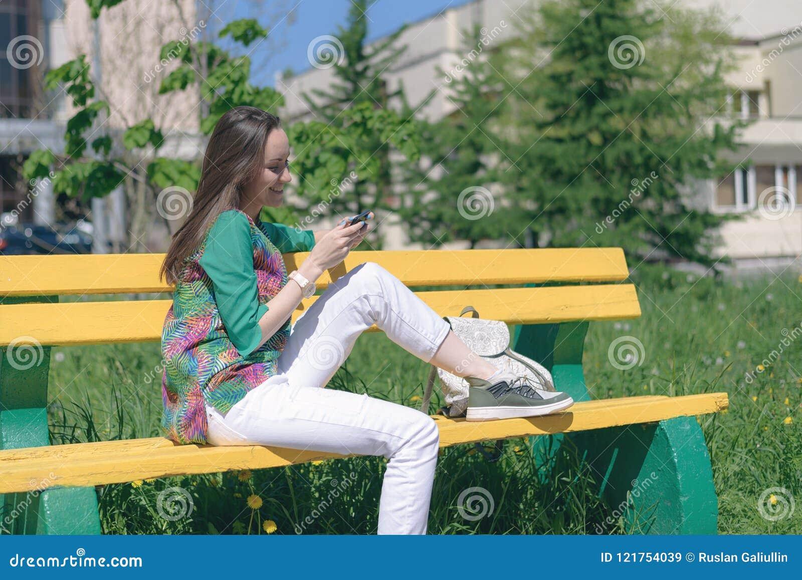 Ung flicka i vit jeans och gymnastikskor som sitter på en gul bänk och bruk en smartphone, online-kommunikation, sociala nätverk,