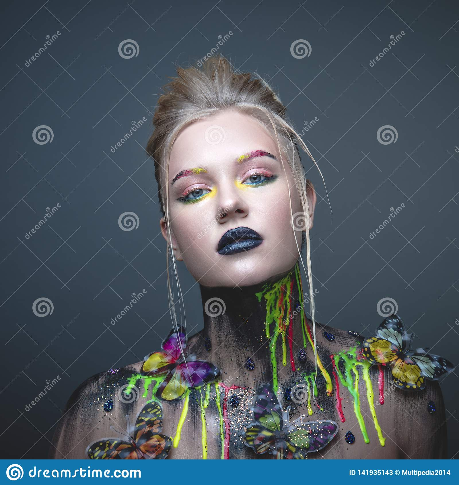 Ung flicka med idérik makeup med fjärilar