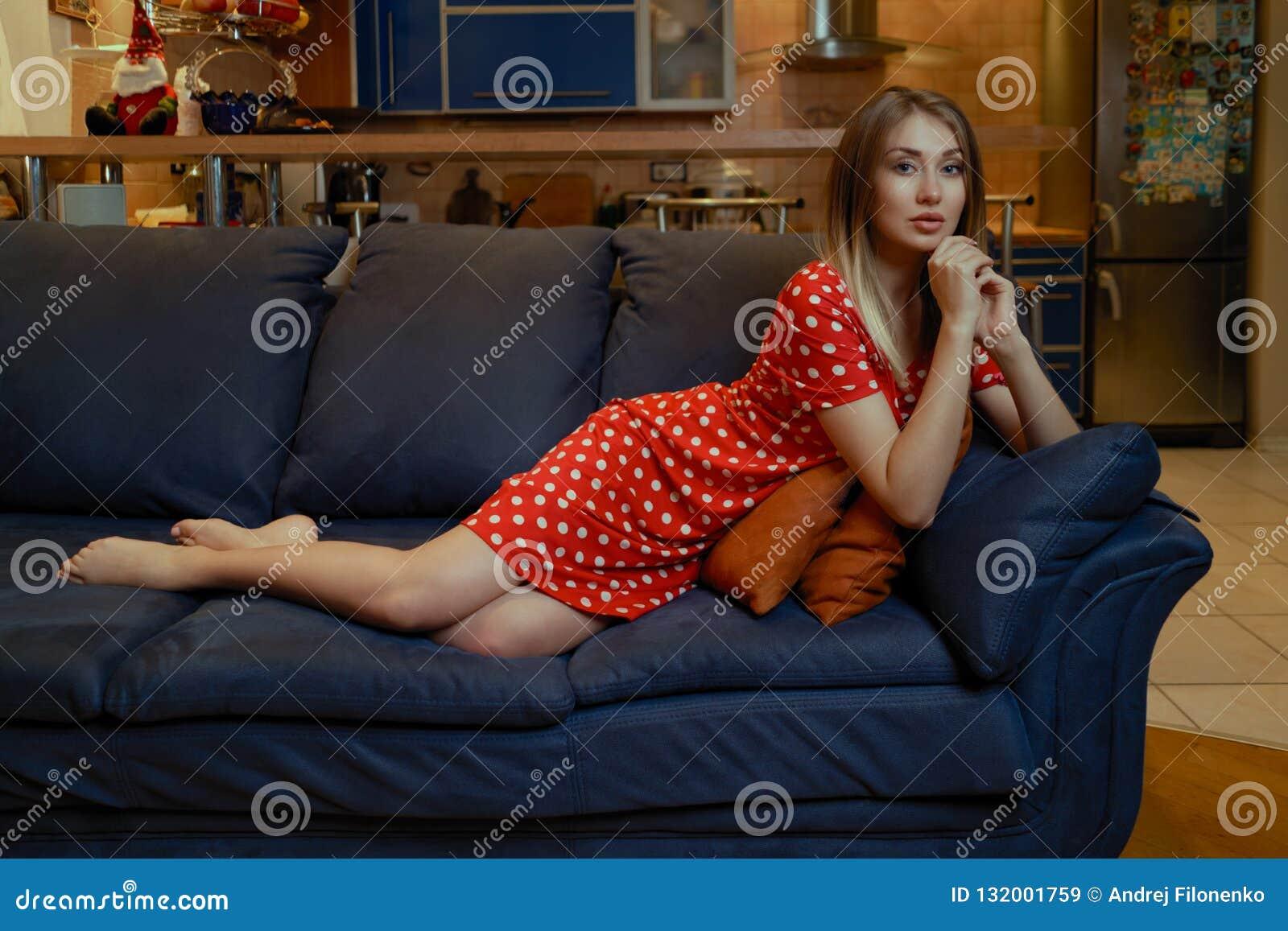 Ung flicka med långt hår i en klänning i röda prickar som poserar att ligga på en blå soffa hemma