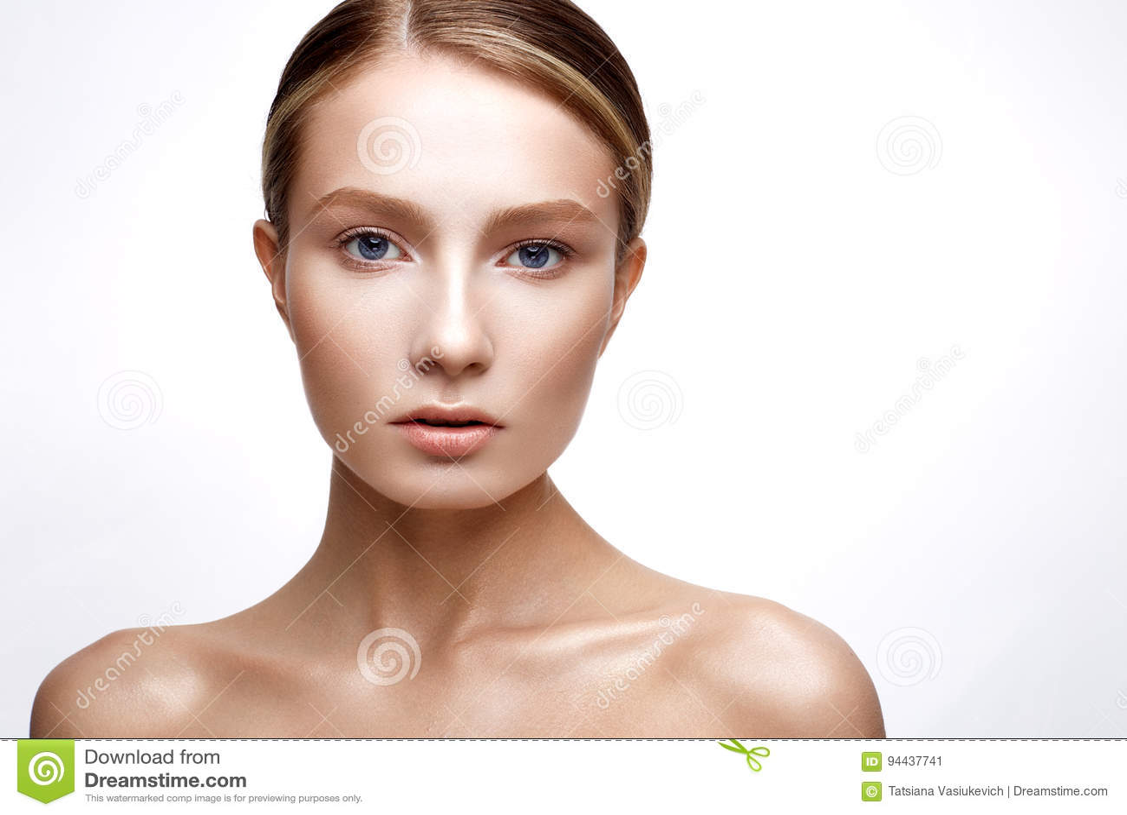 Ung flicka med perfekt glänsande hud En härlig modell med en fundament- och nakenstudiemakeup Rengöringen flår Vit isolerad bakgr